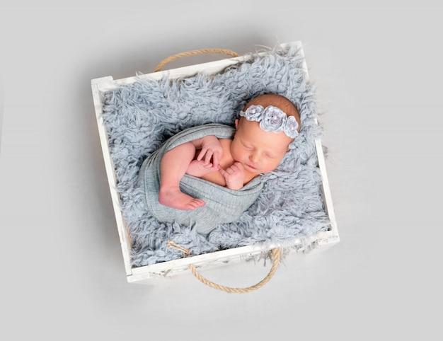 Новорожденная девочка спит в деревянной коробке
