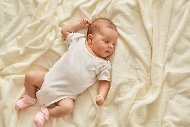 Newborn baby girl or boy lying on blanket on bed looking away, wearing white bodysuit and socks, infant studying world around, has sleepy expression.