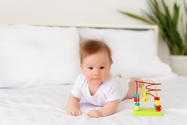 Newborn baby girl boy resting in bed. the child lies on his stomach in bed with a toy. infant