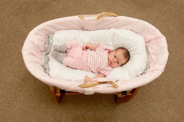 コケのバスケットで生まれたばかりの赤ちゃんの女の子。新生児の医療コンセプト。