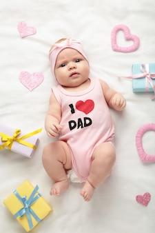碑文とtシャツの生まれたばかりの女の赤ちゃん私はカメラを見てお父さんが大好きです。バレンタイン・デー。上面図