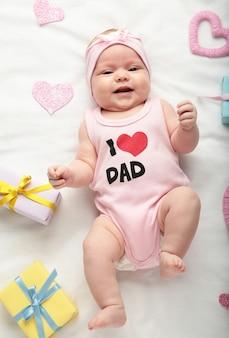 Новорожденная девочка в футболке с надписью я люблю папу