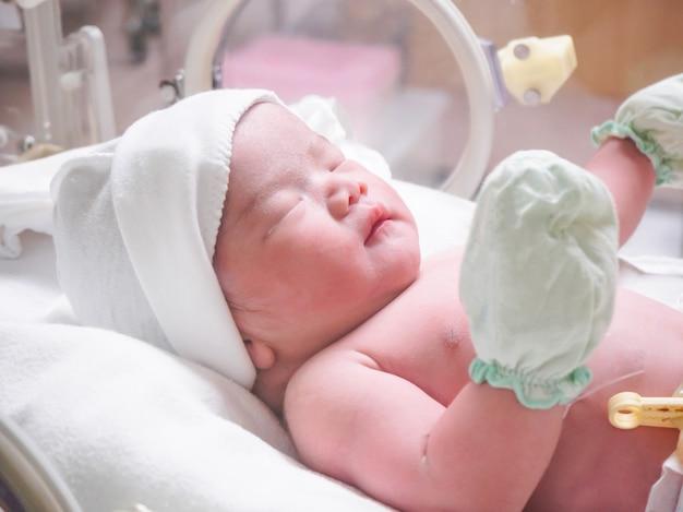 病院の分娩後の部屋のインキュベーター内の生まれたばかりの女の赤ちゃん