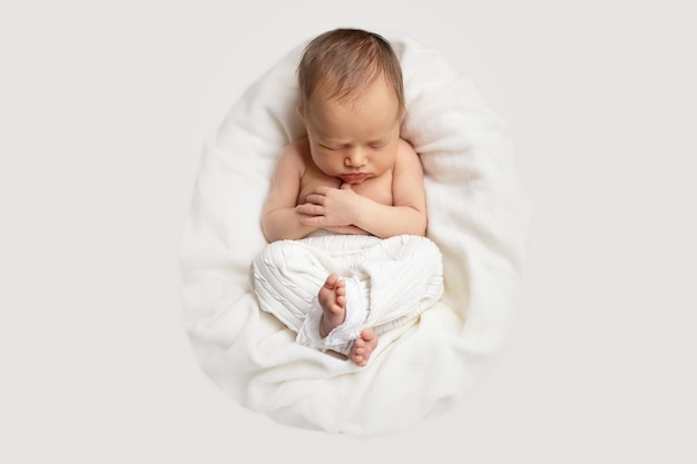 Newborn baby girl is sleeping in the basket on a white blanket and light