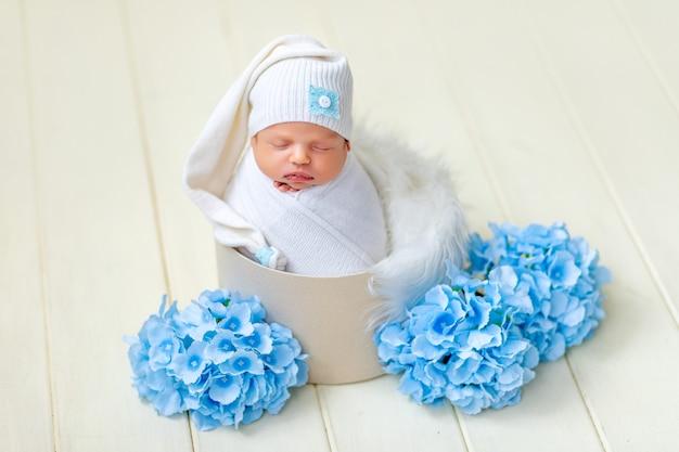 生まれたばかりの女の赤ちゃんは白い毛皮と青い花のバスケットで寝ています