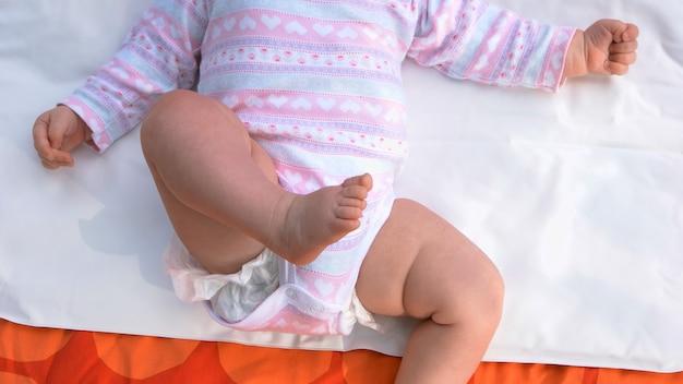 Новорожденная девочка, лежа на спине. крошечные голые ножки младенца. рождение новой жизни и воспитание детей.
