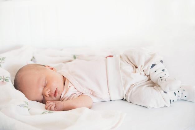 生まれたばかりの女の赤ちゃんは、人生の最初の日を眠ります。安らかに眠っているかわいい新生児