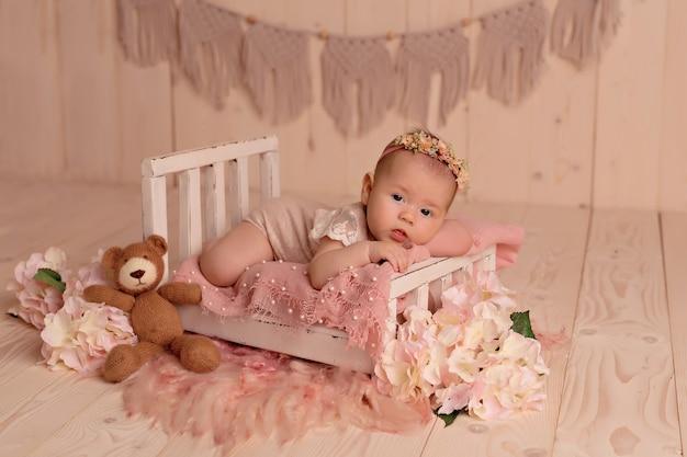 Newborn baby girl sleeping in bed with pink garden flowers