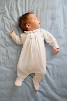 Newborn baby girl sleeping on blue sheets at home