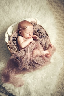 Новорожденная девочка спит в корзине.