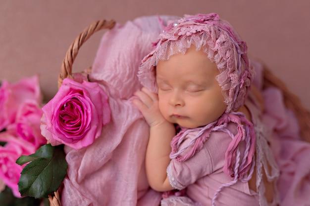 ピンクの庭のバラの花とレトロなバスケットで寝ている生まれたばかりの赤ちゃん女の子