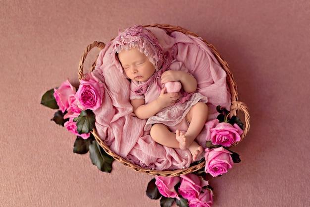 Новорожденная девочка спит в ретро-корзине с цветами розовых садовых роз