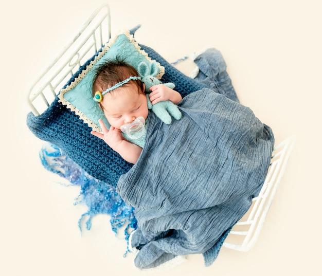 Newborn baby girl sleeping in a little bed