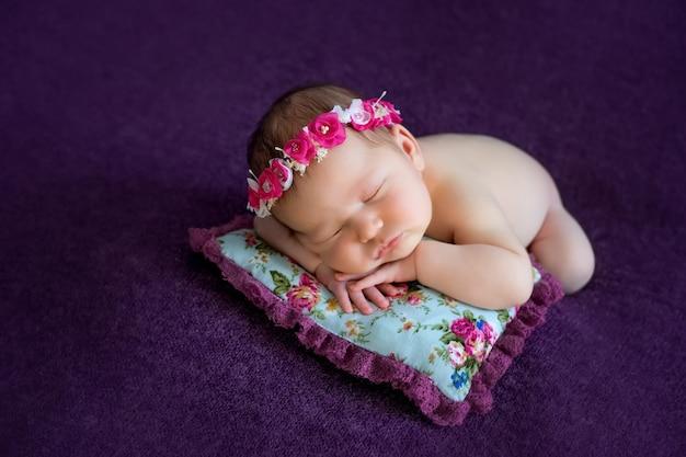 Новорожденная девочка спит на подушке на животе, портрет, 0-14 дней