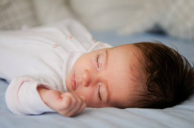 自宅で青いシートで眠っている新生児の女の子