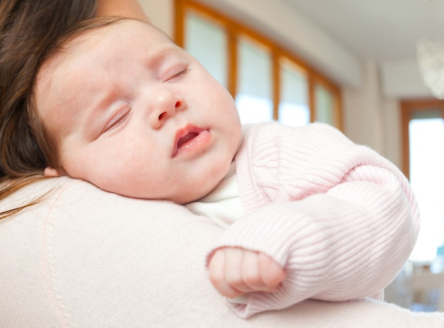 Newborn baby girl sleeping on shoulder