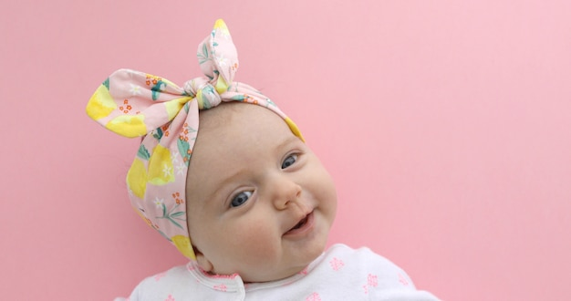 Newborn baby girl smiling pink background