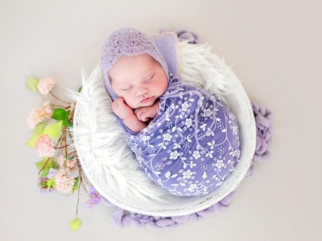 Новорожденная девочка, пеленая в красивую ткань