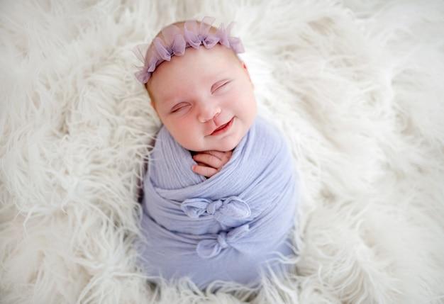 Новорожденная девочка, закутанная в голубую ткань, спит и улыбается