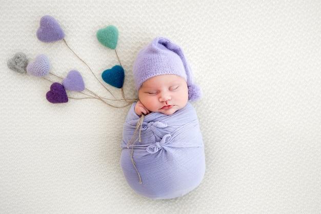 Новорожденная девочка, пеленая в голубой ткани