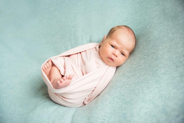 Новорожденную девочку с энтузиазмом смотрят. закрыть
