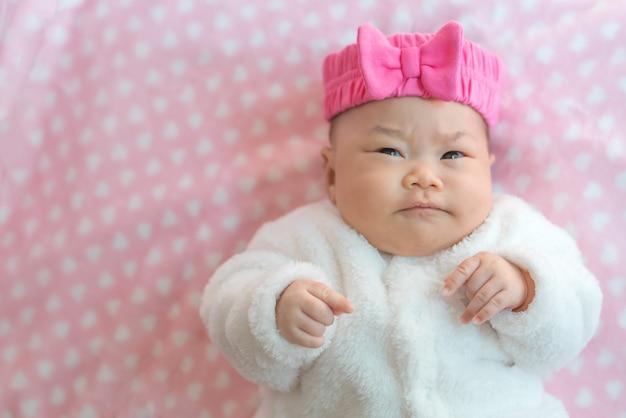生まれたばかりの赤ちゃんの女の子はベッドにセーターとピンクのヘッドバンドを着用します。