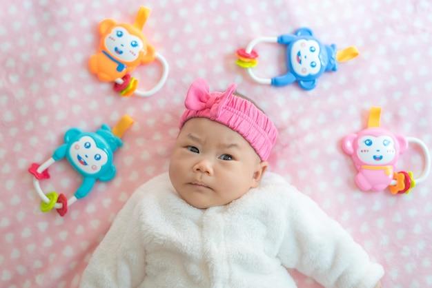 生まれたばかりの赤ちゃんの女の子は子供のおもちゃとベッドの上のセーターとピンクのヘッドバンドを着用します。