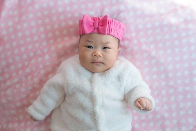 生まれたばかりの赤ちゃん女の子はベッドにセーターとピンクのヘッドバンドを着用します。