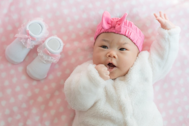 Newborn baby girl wear sweater and pink headband  on a bed with sock.
