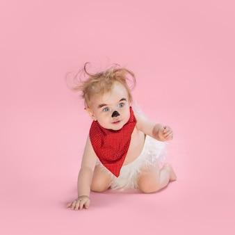 ピンクのスタジオの背景にハロウィーンの衣装を着て生まれたばかりの女の赤ちゃん