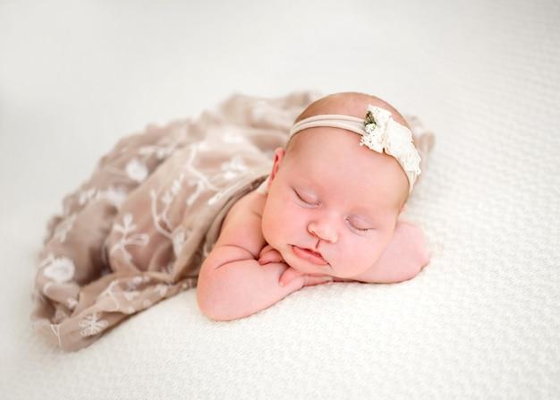 Новорожденная девочка в бежевом платье спит