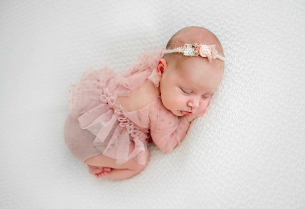 Новорожденная девочка в милом костюме спит