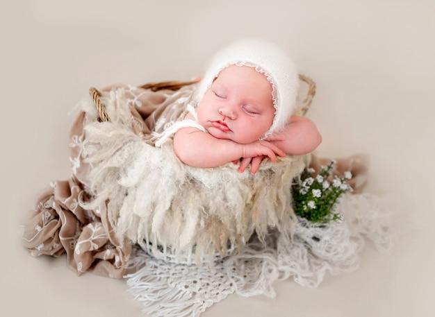 Новорожденная девочка в вязаной белой шапке спит в корзине