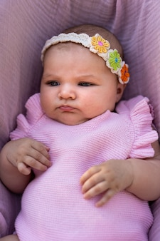 핑크 니트 옷과 꽃 머리 액세서리를 입고 신생아 소녀