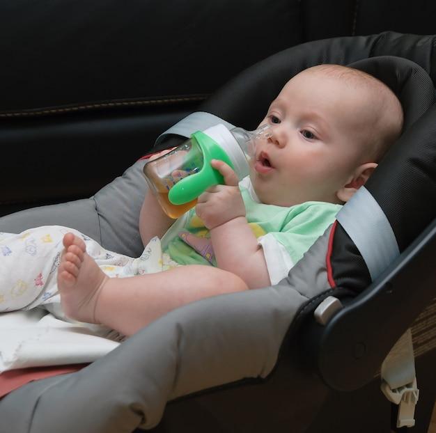 Новорожденный ребенок в автокресле пьет из бутылки
