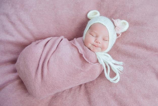 Новорожденный ребенок в белой шляпе с медвежьими ушками сладко спит
