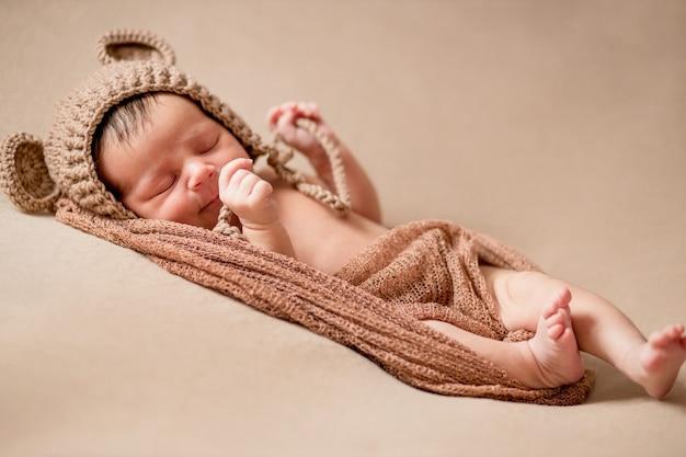 Новорожденный ребенок спит на спине на коричневом одеяле.
