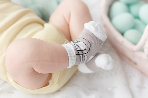 Newborn baby legs in socks on easter eggs background.