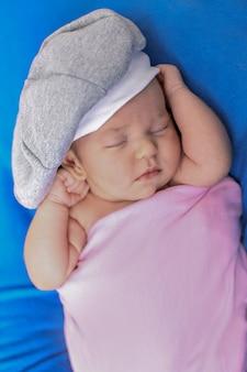 Newborn baby lies in a beautiful hat