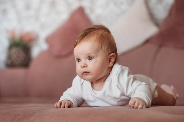 Новорожденный ребенок лежит на диване на животе