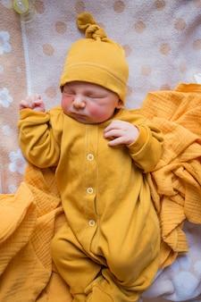 Newborn baby in orange clothes. a child born in the fall. newborn in the hospital