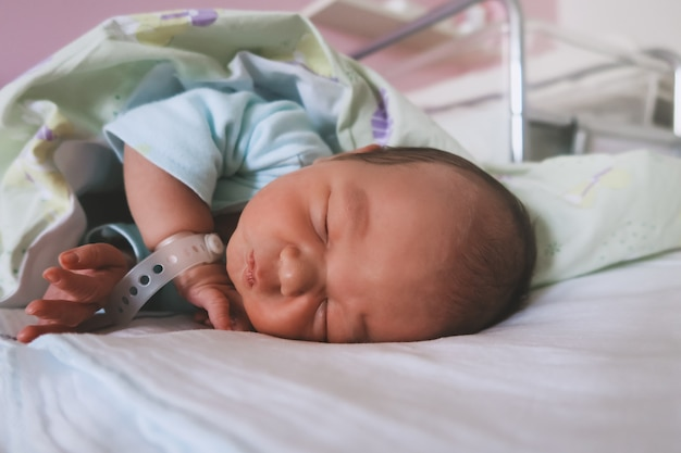 Newborn baby peacefully sleeping in hospital room after delivery