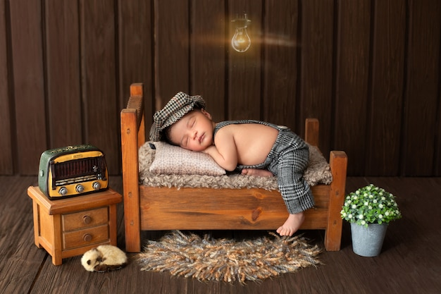 Newborn baby portrait of likeable and pretty baby boy laying on little wooden bed surrounded by flowers radio and cute animal on floor