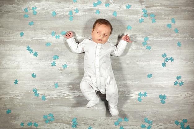 生まれたばかりの赤ちゃんは木の床の青いパズルで静かに眠ります。新生児の穏やかで健康的な睡眠。