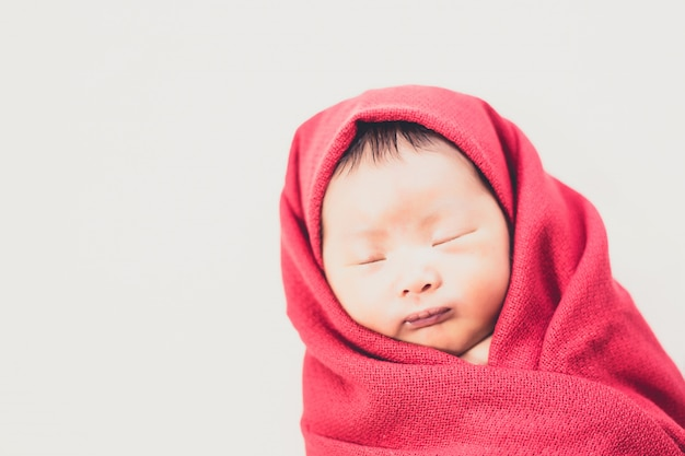Newborn baby in red daiper sleeping on bed