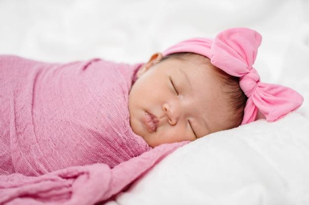 生まれたばかりの赤ちゃんはベッドの上のピンクの布ラップ毛布で眠る