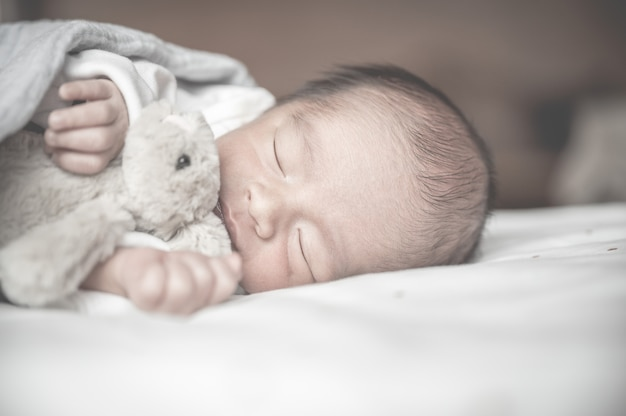 Newborn baby sleeping on bed with little rabbit.family and love concept.asian kid.