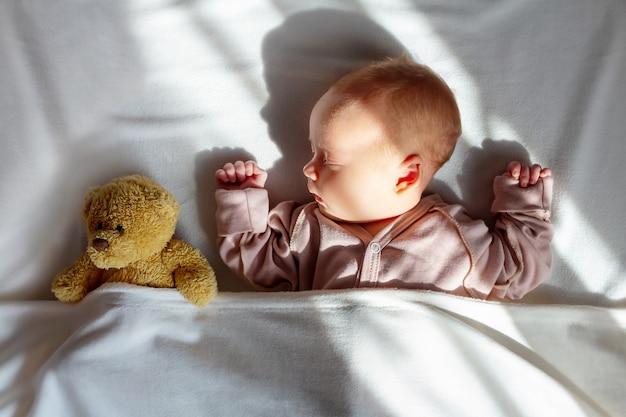 첫 번째 장난감으로 집에서 잠자는 신생아