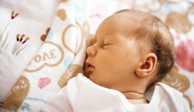 毛布のベビーベッドで眠っている生まれたばかりの赤ちゃん。写真にはあなたのテキストのための空きスペースがあります