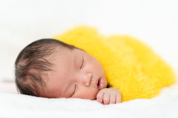 ベッドの上の黄色い毛皮の毛布で眠っている新生児